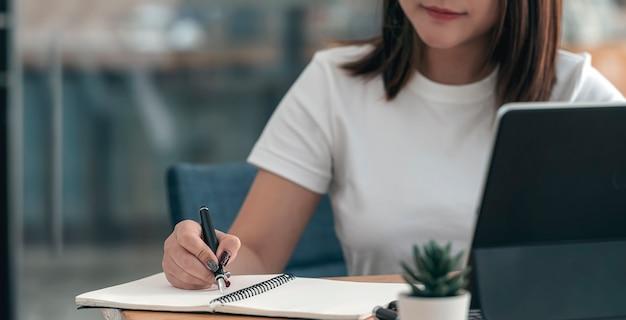 Imange zbliżenie żeński strony pisania na notebooku za pomocą pióra, siedząc przy biurku.