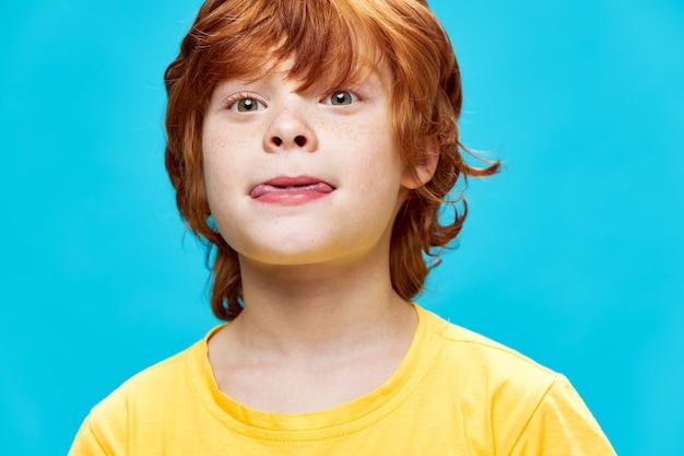 Imbir dziecko z bliska gryzie język żółty t-shirt przycięty widok dzieciństwa