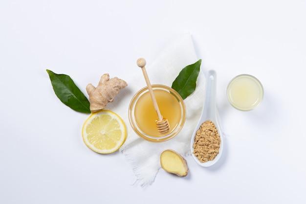 Imbir, miód i cytryna w białych talerzach i łyżce
