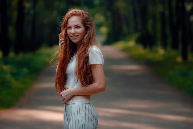 Imbir młoda piękna kobieta pozuje w zielonym lesie
