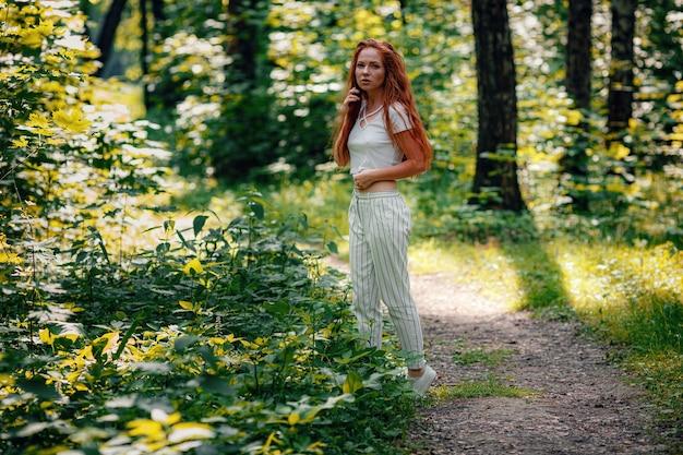 Imbir piękna kobieta w swobodnym stroju pozuje w lesie