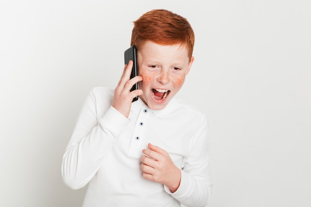 Imbirowa chłopiec krzyczy podczas rozmowy na smartfonie