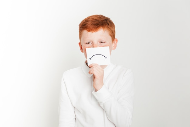 Imbirowa chłopiec mienia karta z smutną twarzą