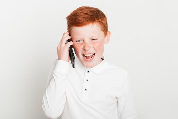 Imbirowa chłopiec robi rozmowie telefonicza