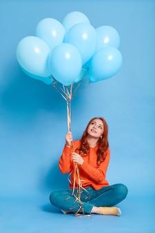 Imbirowa dama w pomarańczowym swetrze trzymająca niebieskie balony z helem i patrząc z uśmiechem w górę, kobieta siedząca na podłodze i świętująca urodziny, pozująca odizolowana na kolorowej ścianie.