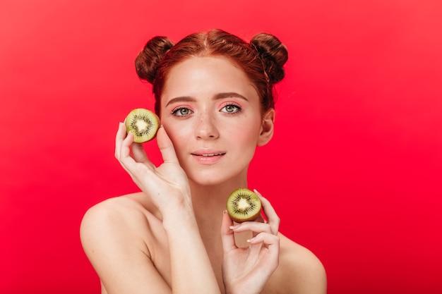 Imbirowa dziewczyna trzyma kiwi. studio strzałów kaukaski urocza kobieta z owocami tropikalnymi.