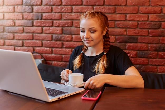 Imbirowa dziewczyna używa laptopa w kawiarni