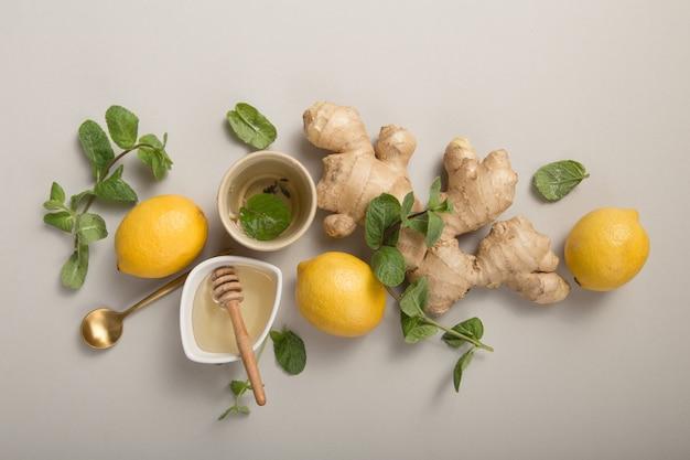 Imbirowa herbata cytrynowa z miodem. rozgrzewająca herbata wzmacniająca odporność z cytrusami i imbirem. puchar, miód, korzeń imbiru na szarym pastelowym tle