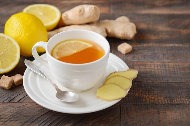 Imbirowa herbata korzeniowa z cytryną i miodem na drewnianym stole.
