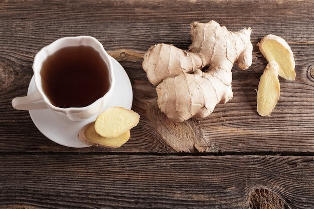 Imbirowa herbata w białej filiżance na drewnianym tle