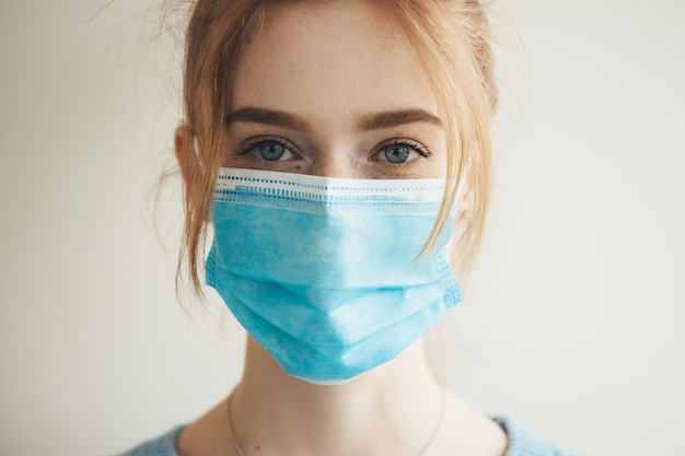 Imbirowa kaukaska kobieta z piegami w masce medycznej z filtrem pozuje na białej ścianie studia