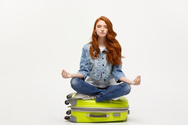 Imbirowa kobieta medytuje w lotos pozie na bagażu valise. pojedynczo na białym.