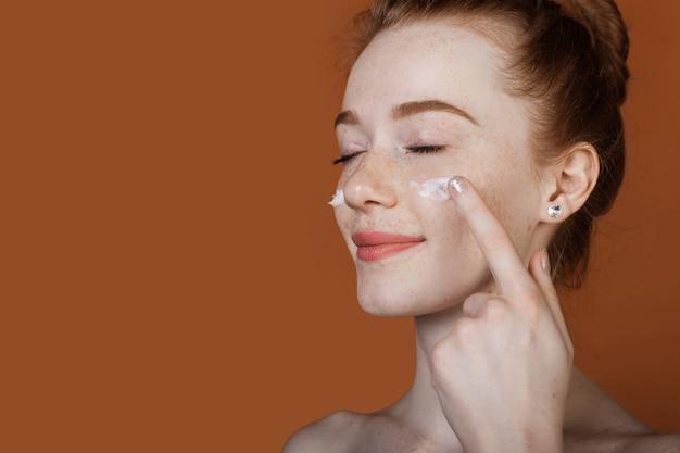 Imbirowa kobieta nakładająca krem przeciwzmarszczkowy na twarz z zamkniętymi oczami na brązowej ścianie studia z wolną przestrzenią