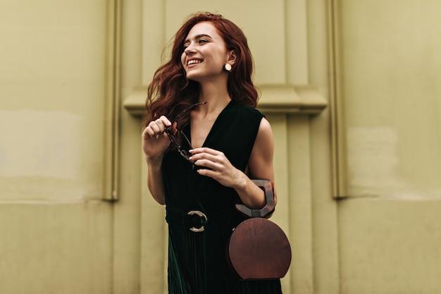 Imbirowa kobieta trzyma torebkę i uśmiecha się