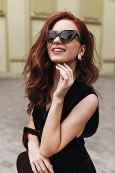 Imbirowa kobieta w modnych okularach przeciwsłonecznych pozuje na zewnątrz i uśmiecha się