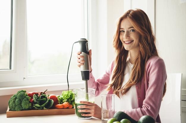 Imbirowa kobieta z piegami, używając wyciskarki elektrycznej i uśmiechając się, robiąc świeży sok warzywny