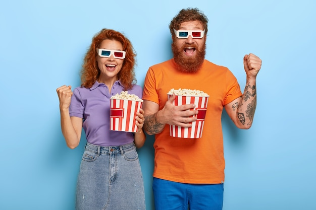 Imbirowa para pozuje z popcornem i okularami