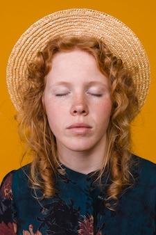 Imbirowa piegowata kobieta w kapeluszu z zamkniętymi oczami