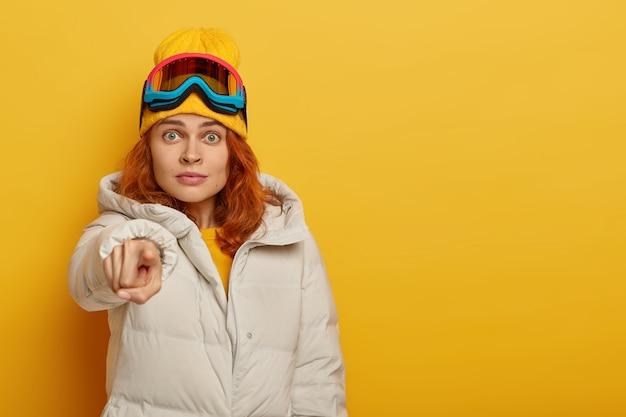 Imbirowa snowboardzistka pod wrażeniem wskazuje na aparat, ubrana w odzież wierzchnią, ochronne okulary snowboardowe, odizolowane na żółtym tle. koncepcja ośrodka zimowego