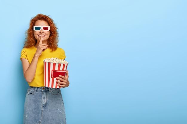 Imbirowa urocza dziewczyna trzyma wiadro z popcornem