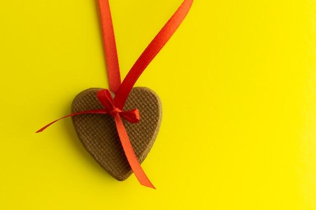 Imbirowe ciasteczka kształt serca z czerwoną wstążką na jasnym żółtym tle.