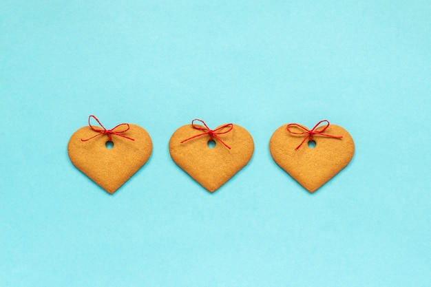 Imbirowe ciasteczka w kształcie serca ozdobione kokardą na niebieskim tle valentine karty