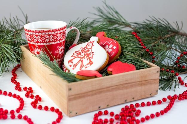 Imbirowe herbatniki i filiżanka herbaty na stole z gałązkami świerku