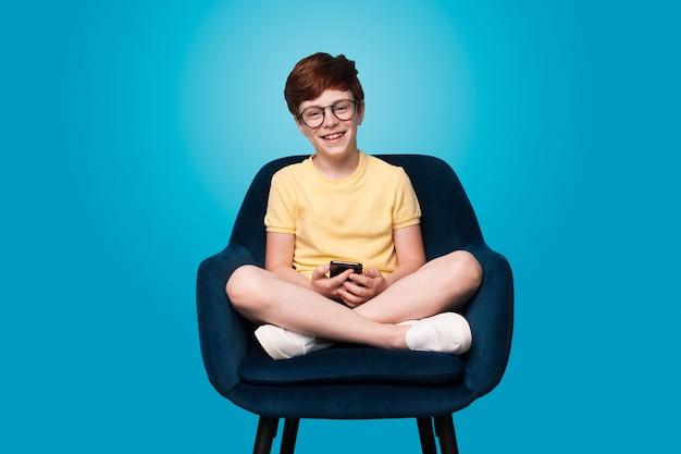 Imbirowy chłopiec siedzi w fotelu i noszenie okularów