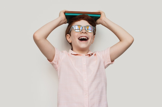 Imbirowy chłopiec w okularach trzyma jakieś książki na głowie