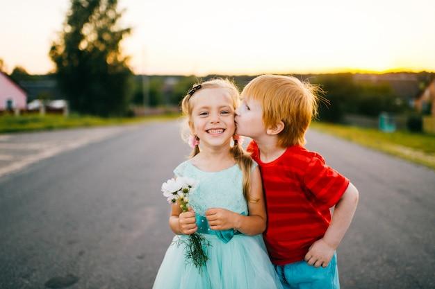 Imbirowy facet z bladą skórą kising mało nieśmiałą piękną dziewczyną w błękitnej wakacje sukni plenerowej na drodze w wsi przy seunset na abstrakcjonistycznym tle. jesień na terenach wiejskich. śmieszne szczere dzieciaki.