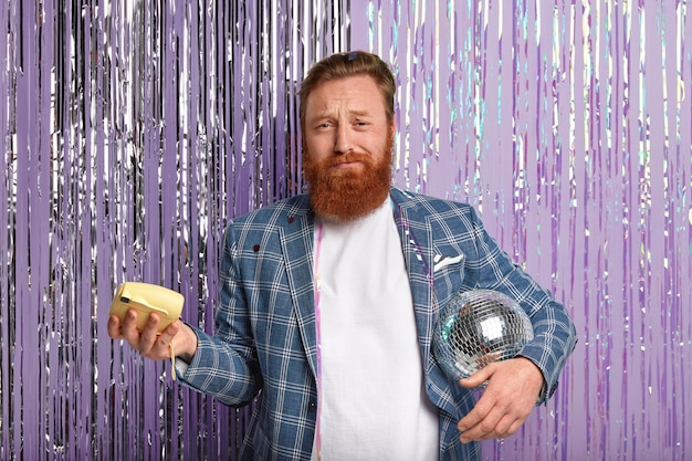 Imbirowy mężczyzna na imprezie trzyma kulę disco i kamery