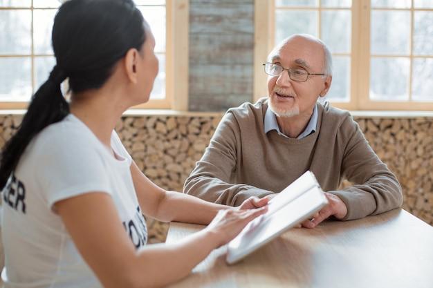 Imponująca książka. zadowolony zadowolony starszy mężczyzna w okularach słuchając wolontariusza i siedząc przy stole