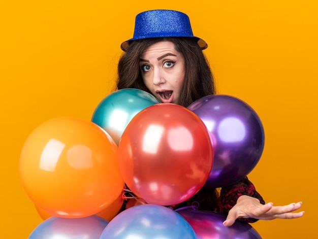 Imponująca młoda imprezowa dziewczyna w imprezowym kapeluszu stojąca za balonami, patrząca na kamerę wyciągającą rękę odizolowaną na pomarańczowej ścianie