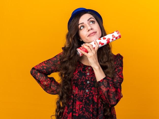 Imponująca młoda imprezowa dziewczyna w imprezowym kapeluszu trzymająca rękę na talii, patrząc w górę, dotykając podbródka z armatą konfetti odizolowaną na pomarańczowej ścianie