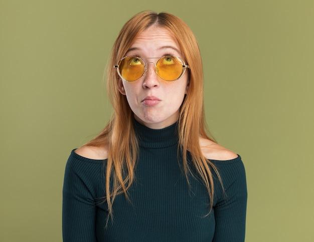 Imponująca młoda rudowłosa ruda dziewczyna z piegami w okularach przeciwsłonecznych patrząca w górę odizolowana na oliwkowozielonej ścianie z miejscem na kopię