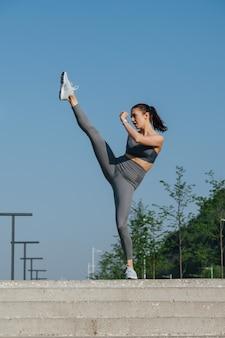 Imponująco wysportowana brunetka ćwicząca na świeżym powietrzu, podnosząca wysoko nogę
