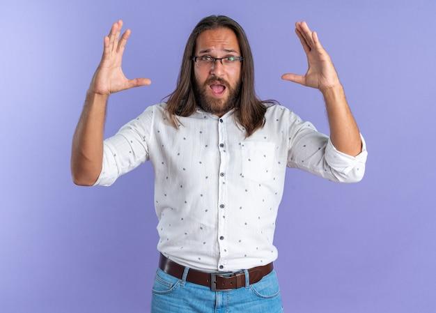 Imponujący dorosły przystojny mężczyzna w okularach, patrzący na aparat trzymający ręce w powietrzu na fioletowej ścianie