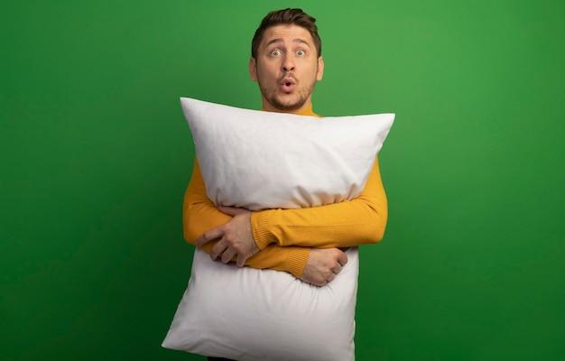 Imponujący młody blond przystojny mężczyzna przytula poduszkę, patrząc prosto