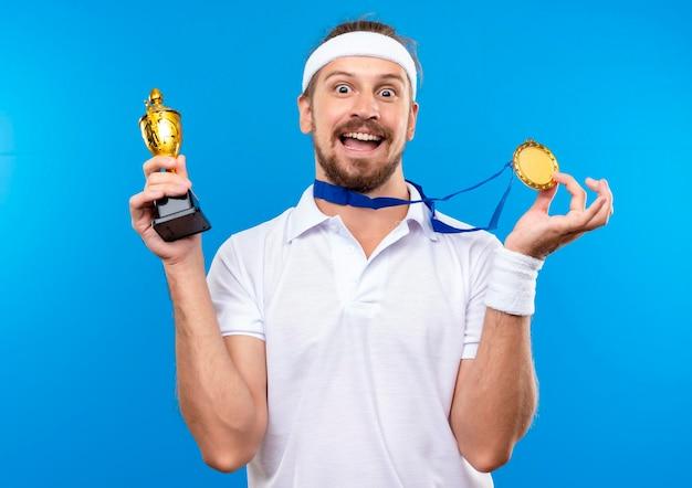 Imponujący młody przystojny sportowy mężczyzna noszący opaskę na głowę i opaski oraz medal na szyi, trzymający medal i puchar zwycięzcy na niebieskiej ścianie