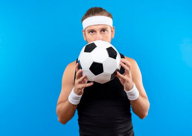 Imponujący młody przystojny sportowy mężczyzna noszący opaskę na głowę i opaski, trzymający piłkę nożną i chowający się za nią na białym tle na niebieskiej ścianie