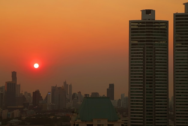 Imponujący widok na jasne słońce na złotym niebie nad miastem