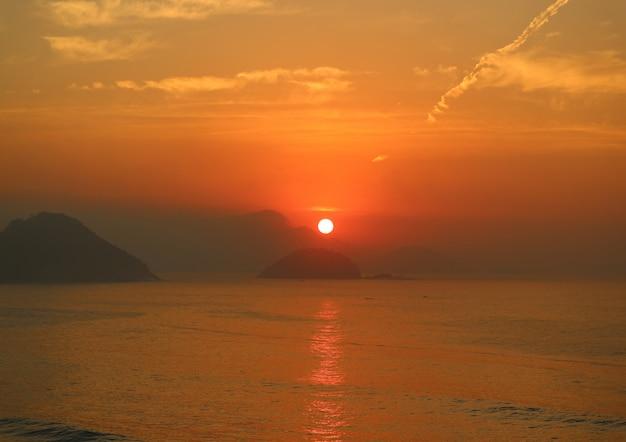 Imponujący wschód słońca nad widokiem na ocean atlantycki z plaży copacabana w rio de janeiro, brazylia