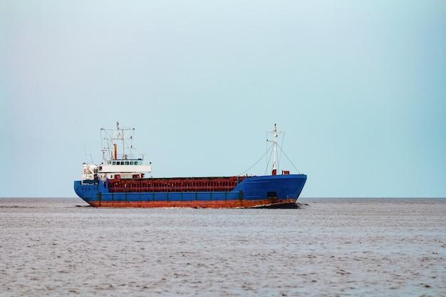 Import towarów. duży niebieski statek towarowy przemieszcza się do portu w rydze