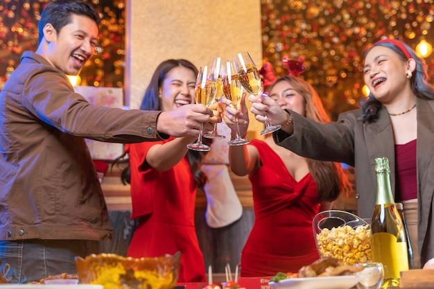 Impreza azjatyckich przyjaciół cieszących się świątecznymi napojami i świętujących zbliżenie kieliszków brzęczących