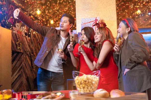 Impreza azjatyckich przyjaciół delektujących się świątecznymi napojami i świętująca robienie selfie przez smartfona