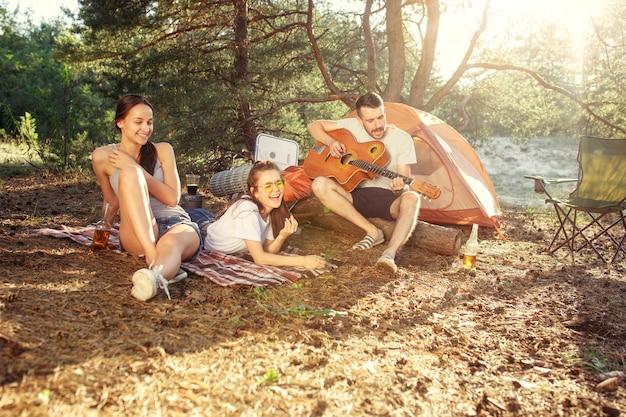 Impreza, biwakowanie grupy mężczyzn i kobiet w lesie. relaksują się, śpiewając piosenkę na tle zielonej trawy. wakacje, lato, przygoda, styl życia, koncepcja pikniku