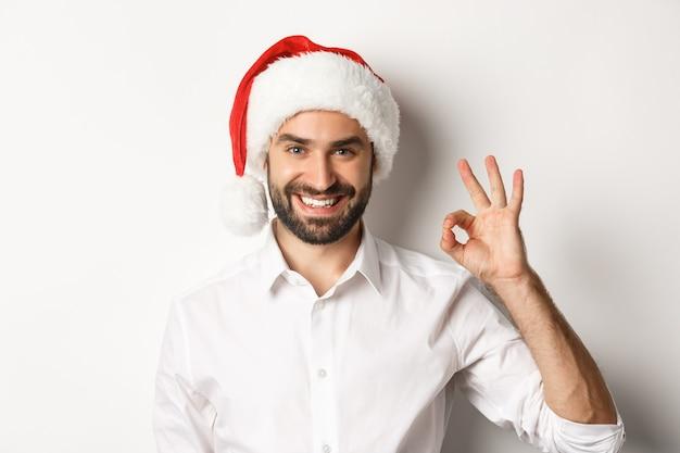 Impreza, ferie zimowe i koncepcja uroczystości. pewny siebie mężczyzna w czapce świętego mikołaja pokazuje dobrze podpisać, zatwierdzić i polubić