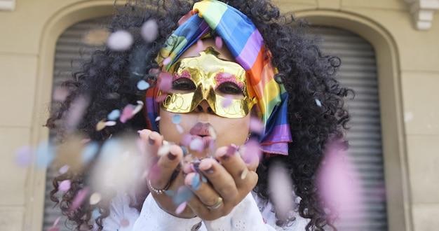 Impreza karnawałowa. brazylijski kręcone włosy kobieta w stroju dmuchanie konfetti.