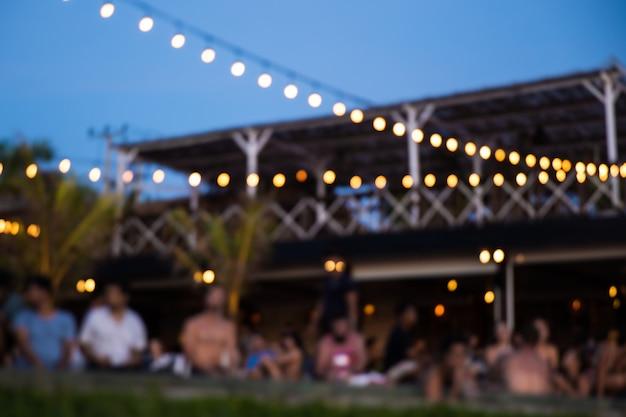 Impreza na plaży o zachodzie słońca z przyjaciółmi przy basenie z widokiem na ocean. niewyraźne tło.
