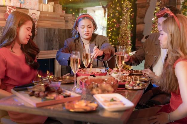 Impreza pięknej azjatyckiej przyjaciółki kobiety i mężczyzny świętującej kobietę serwującą pizzę na stole